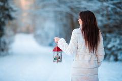 Girl holding Christmas lantern outdoors on beautiful winter snow day Stock Photos