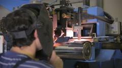 Worker controls plasma welding machine, welding metal parts Stock Footage