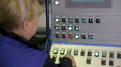 Female worker operating industrial control panel, display at a modern industrial Stock Footage