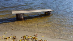 Flood water from river surrounds old bench Stock Footage