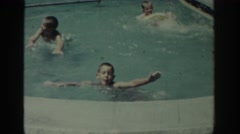1962: video of family at public pool, swimming and splashing in the shallow end Stock Footage