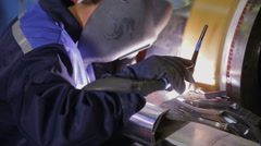 Welder welding metal at a electric engine production factory Stock Footage