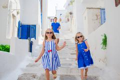 Family vacation in Europe. Father and kids at narrow street on Mykonos Island Stock Photos
