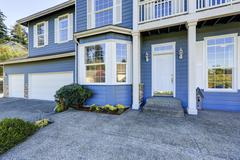Blue house exterior. View of entrance porch with concrete floor and white wic Stock Photos