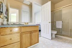 Wooden vanity cabinet, glass shower and a toilet. Bathroom interior. There is Stock Photos