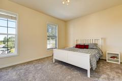 Simple upstairs bedroom with soft peach walls, gray carpet and white wooden b Stock Photos