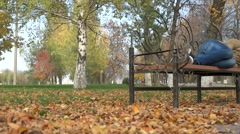 Man asleep on a bench in the park Stock Footage