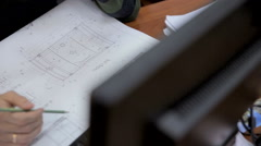 Architect working with blueprints, sketchs, drawings sitting at a desk near Stock Footage