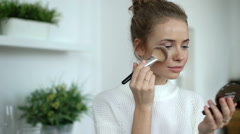 Beauty woman applying makeup. Beautiful girl applying cosmetic with a big brush. Stock Footage