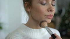 Portrait Of Blue-eyed Blonde Woman applying make-up Stock Footage
