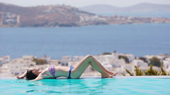 Beautiful young girl relaxing on the edge of swimming pool outdoors Stock Footage