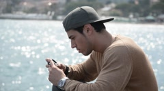 Athletic man at the seaside using cell phone to type message Stock Footage
