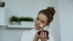 Blonde woman applying her makeup with the brush Stock Footage