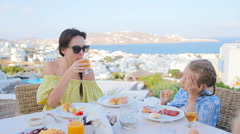 Family having breakfast at outdoor cafe with amazing view on Mykonos town Stock Footage