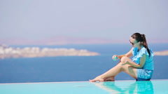 Slim woman applying sunscreen on her legs, sitting on the edge of pool Stock Footage