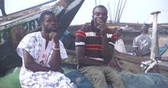 Ghanaian fishermen restingin port Stock Footage