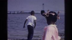 1976: group of children on the beach, searching for worms in the dirt. HARLEM Stock Footage