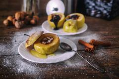 Stuffed baked apple with nuts, honey and chocolate on white dessert plates, dark Stock Photos