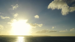 Wide shot of a sunset in timelapse over ocean and cliffs. Progressive zoom. Stock Footage