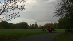 Cyclist is Sitting on a Bench by Footpath Park Alley Having Rest in Cloudy Stock Footage