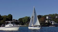 Sailboat and motorboat on the water, warm breezy autumn day Stock Footage