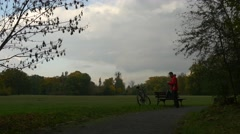 Cyclist Tourist at the Bench Going to Leave Gets on the Bicycle and Riding Away Stock Footage