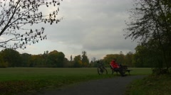 Bored Cyclist Sitting on the Bench in Cloudy Day Park Man is Resting at the Stock Footage