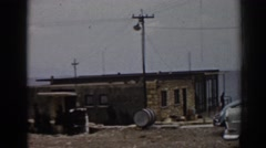 1962: coastal building near large body of water, man standing on porch EPHESUS Stock Footage