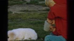 1962: boy feeding puppy dog at barracks style living EPHESUS TURKEY Stock Footage