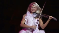 The actress plays the violin, she is dressed in a sparkling dress with light Stock Footage