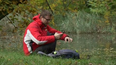 Man is Texting on Mobile Phone Autumn Landscape Sitting in Park on a Ground by Stock Footage