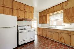 Interior of old fashioned kitchen room with linoleum floor , wooden cabinets  Stock Photos
