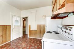 Interior of old style kitchen with linoleum floor and wooden paneled wall tri Stock Photos