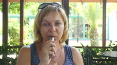 Woman vaping in outdoor cafe, slow motion 1 Stock Footage