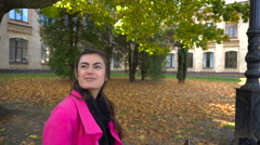 Young girl in pink coat with laptop on bench in university park Stock Footage