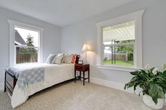 Bright neatly arranged bedroom with single bed and carpet floor. Northwest, U Stock Photos