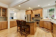 Bright wooden kitchen room with stainless steel appliances, kitchen island wi Stock Photos