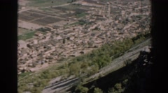 1962: a built-up area lies at the base of a tree studded steep mountain slope Stock Footage