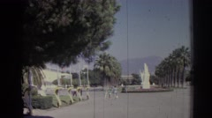 1962: people milling about in a courtyard with a statue and rows of trees IZMIR Stock Footage