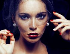 Beauty brunette woman under black veil with red manicure close u Stock Photos