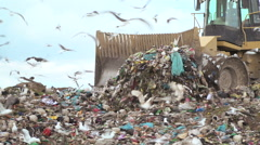 Bulldozer moving waste across a landfill site Stock Footage