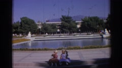 1962: twin girls sitting on a bench in a garden like place with water IZMIR Stock Footage