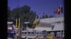 1962: a multi-story building flies many turkish flags and has buses parked  Stock Footage