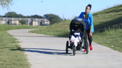 Mother jogging with her baby in the stroller has knee pain Arkistovideo