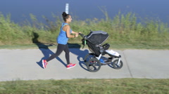 Mom jogging and pushing stroller Stock Footage