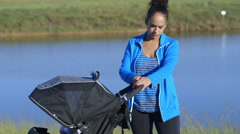 Young mother at the park with her baby in the stroller Stock Footage