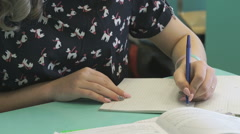 Student writes in her copybook at the lesson Stock Footage