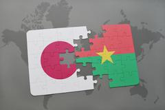 Puzzle with the national flag of japan and burkina faso on a world map backgr Stock Photos