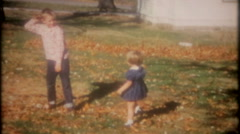 Children play in the fall leaves in the frontyard 3742 vintage film home movie Stock Footage