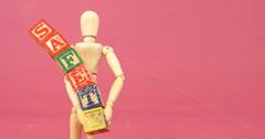 Figurine holding alphabet toy block Stock Footage